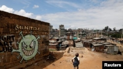 FILE - A boy walks in front of a graffiti promoting the fight against the coronavirus disease, in the Mathare slums of Nairobi, Kenya, May 22, 2020. Kenya reimposed some COVID-19 lockdown restrictions on March 26, 2021.