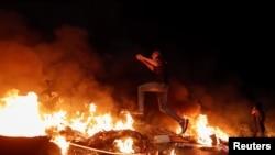 Palestinski demonstrant preskače zapaljenu barikadu tokom protivizraelskog protesta zbog napetosti u Jeruzalemu, u blizini židovskog naselja Beit El u blizini Ramale, na zapadnoj obali, okupiranoj Izraelom, 9. maj 2021. godine.