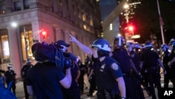 A police officer shouts at Associated Press videojournalist Robert Bumsted, Tuesday, June 2, 2020, in New York. New York City police officers surrounded, shoved and yelled expletives at two Associated Press journalists covering protests Tuesday in…
