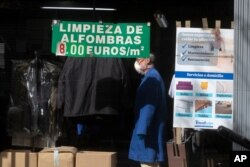 A man works in a dry-cleaners with sign advertising carpet cleaning, centre, in Madrid, Spain, May 4, 2020.