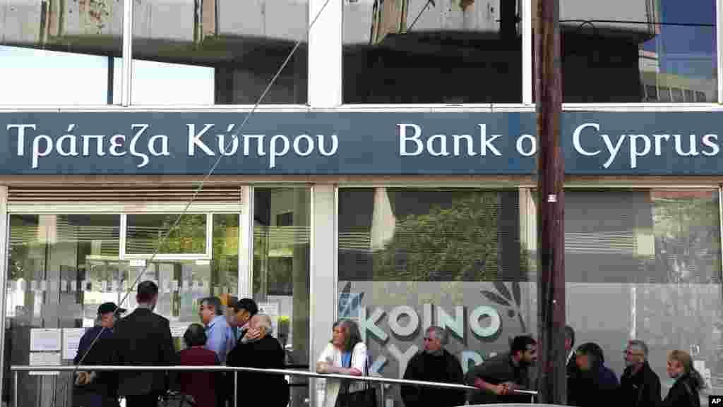 2013年3月28日,人们等在塞浦路斯银行在首都尼克西亚的一家支行门外。