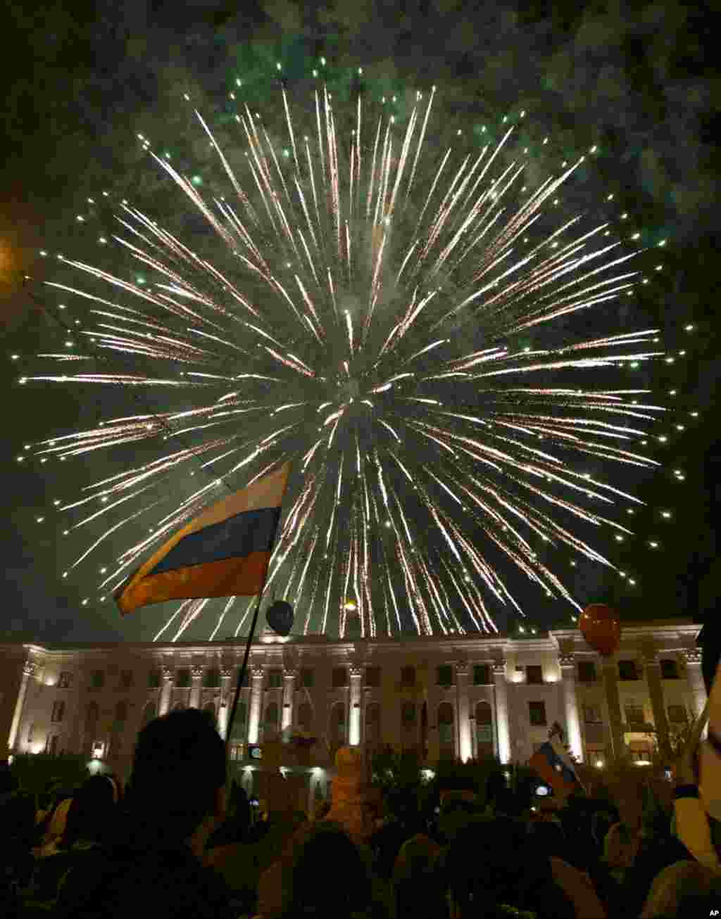 People watch fireworks at the central Lenin Square in Simferopol, Crimea, Mar, 21, 2014. Russian President Vladimir Putin completed the annexation of Crimea, signing a law making the Black Sea peninsula part of Russia.