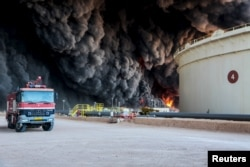 FILE - Fire rises from an oil tank in the port of Es Sider, in Ras Lanuf, Libya, Jan. 6, 2016. A Petroleum Facilities Guards blamed the blazes on attacks by Islamic State militants.