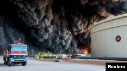 FILE - Fire rises from an oil tank in the port of Es Sider, in Ras Lanouf, Libya, Jan. 6, 2016. A Petroleum Facilities Guards blamed the blazes on attacks by Islamic State militants.