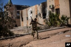 FILE - A fighter of the Libyan forces, affiliated with the Tripoli government, runs for cover while fighting against Islamic State positions in Sirte, Libya, Sept. 22, 2016.