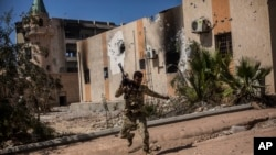 FILE - A fighter of the Libyan forces, affiliated with the Tripoli government, runs for cover while fighting against Islamic State positions in Sirte, Libya, Sept. 22, 2016. IS forces have since been dispersed, yet they can thrive in porous security conditions like those that exist today in Libya, said Frederic Wehrey, a senior fellow at the Carnegie Endowment for International Peace.