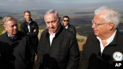 FILE - Israeli Prime Minister Benjamin Netanyahu, center, Republican U.S. Sen. Lindsey Graham, left, and U.S. Ambassador to Israel David Friedman, right, visit the border between Israel and Syria at the Israeli-held Golan Heights, March 11, 2019.