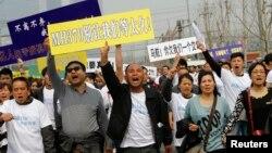 Kerabat penumpang pesawat Malaysia di China menggelar aksi protes di depan Kedutaan Malaysia di Beijing hari Selasa (25/3).
