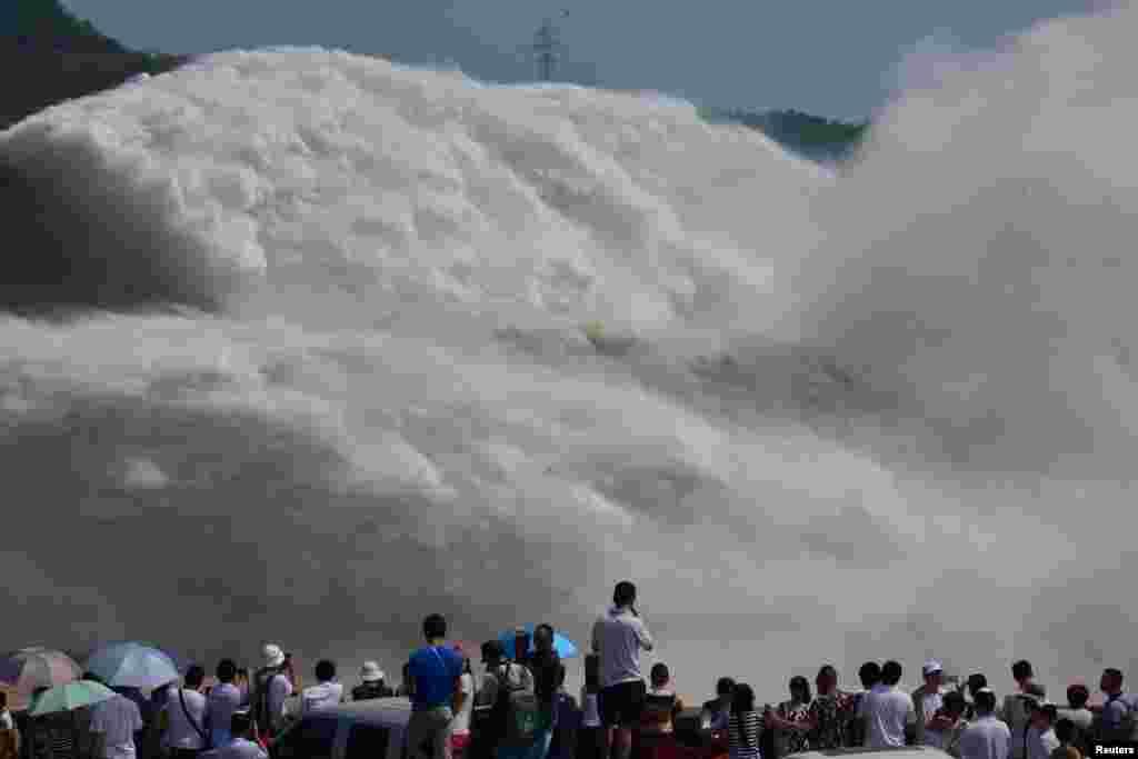 Para pengunjung mengamati semburan air dari waduk Xiaolangdi di Sungai Kuning di Luoyang, Henan, China.