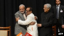 Indian Prime Minister Narinder Modi, left, and Jammu and Kashmir Deputy Chief Minister Nirmal Singh, center, embrace as Jammu and Kashmir Chief Minister Mufty Mohammed Sayeed looks on during a swearing-in ceremony of the state assembly in Jammu, March 1, 2015.