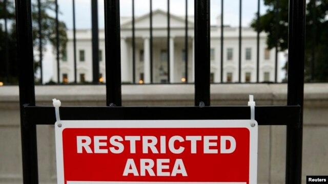 Un rótulo advierte mantener la distancia con la baranda que rodea la Casa Blanca. Un informe revela la necesidad de aumentar la altura del muro para mejorar la seguridad.