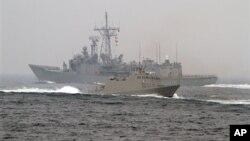 """台湾海军""""光华-6""""型导弹快艇(前)在高雄附近海域举行的演习期间从一艘佩里级护卫舰旁驶过。(2013年1月22日)"""