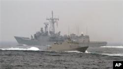 """台灣海軍""""光華-6""""型導彈快艇(前)在高雄附近海域舉行的演習期間從一艘佩里級護衛艦旁駛過。(2013年1月22日)"""