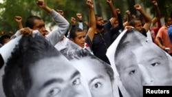 Para pedemo mengacungkan tinju sementara para kerabat dari 43 mahasiswa Sekolah Pelatihan Guru Ayotzinapa, memperingati 6 tahun hilangnya para pelajar itu di Mexico City, Sabtu, 26 September 2020. (Foto: Reuters)