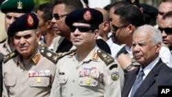 지난 달 이집트 카이로에서 무장세력의 공격으로 사망한 경찰 고위 관계자의 장례식에 참석한 압둘 파타 알시시 이집트 국방장관(가운데)와 하젬 엘베블라위 임시 총리(오른쪽).