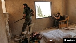 Free Syrian Army fighters take cover inside a house near the air force intelligence headquarters in Aleppo, Syria, August 1, 2013.