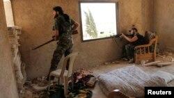 ນັກລົບກອງທັບປົດປ່ອຍຊີເຣຍຄວບຄຸມຢູ່ທາງໃນຂອງເຮືອນຫລັງນຶ່ງ ຢູ່ໃກ້ສໍານັກງານສືບລັບຂອງກອງທັບອາກາດໃນເມືອງ Aleppo ຂອງຊີເຣຍ ໃນວັນທີ 1 ສິງຫາ 2013.