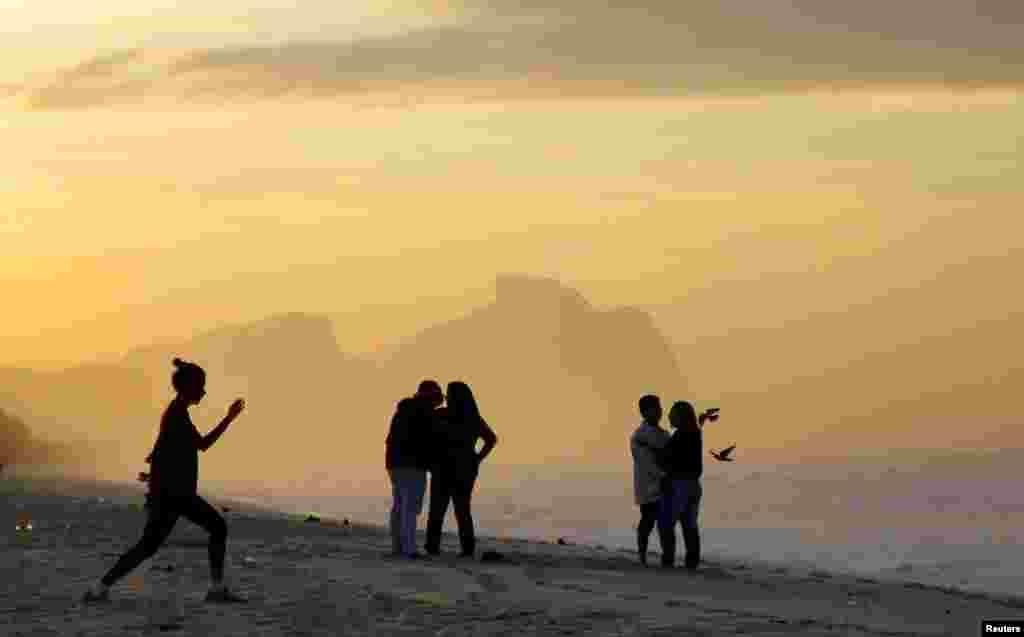People are pictured during sunrise on a beach at the Parque Natural Municipal de Marapendi natural reserve near the Olympic park for the Rio 2016 Summer Olympic Games in Rio de Janeiro, Brazil.