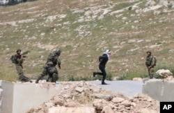 Handcuffed and blindfolded Osama Hajahjeh, 16, runs away from Israeli soldiers near the village of Tekoa, West Bank, Apri 18, 2019.