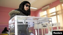 A woman casts her ballot at a polling station in Ardiyah, Kuwait, December 1, 2012.
