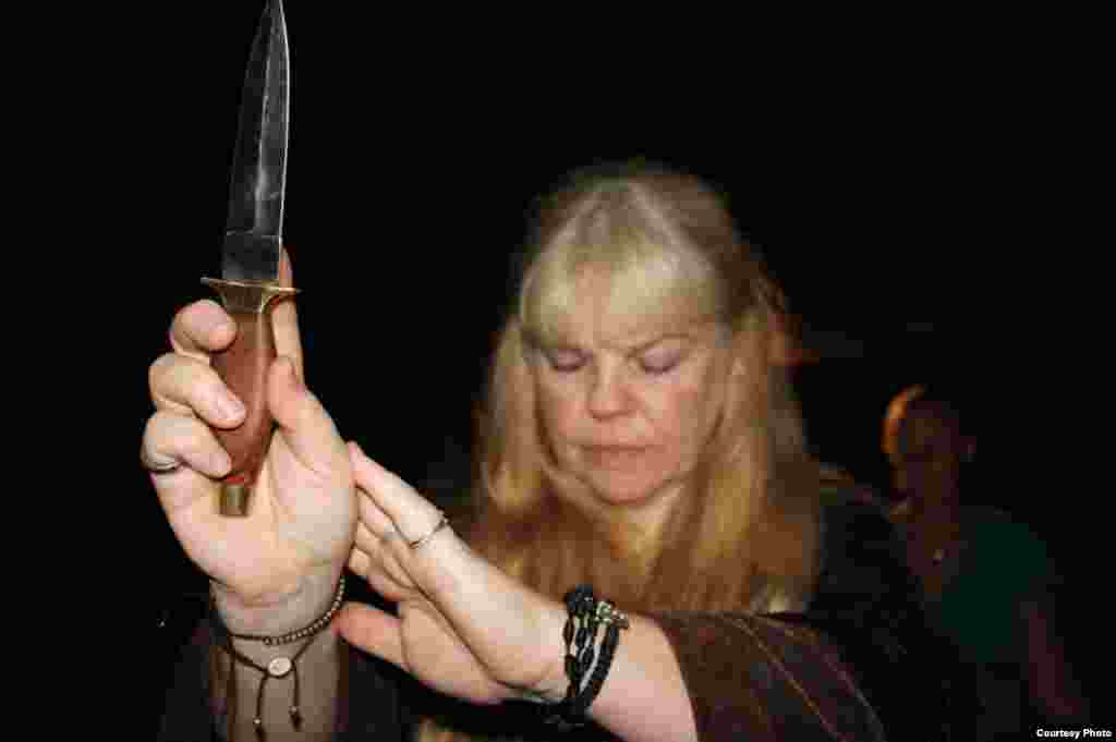 """The high priestess holds up a ceremonial dagger to invoke aspects ofthe rites of ancient elders. """"Most of us in this coven come from ancient Celtic roots,"""" she said."""