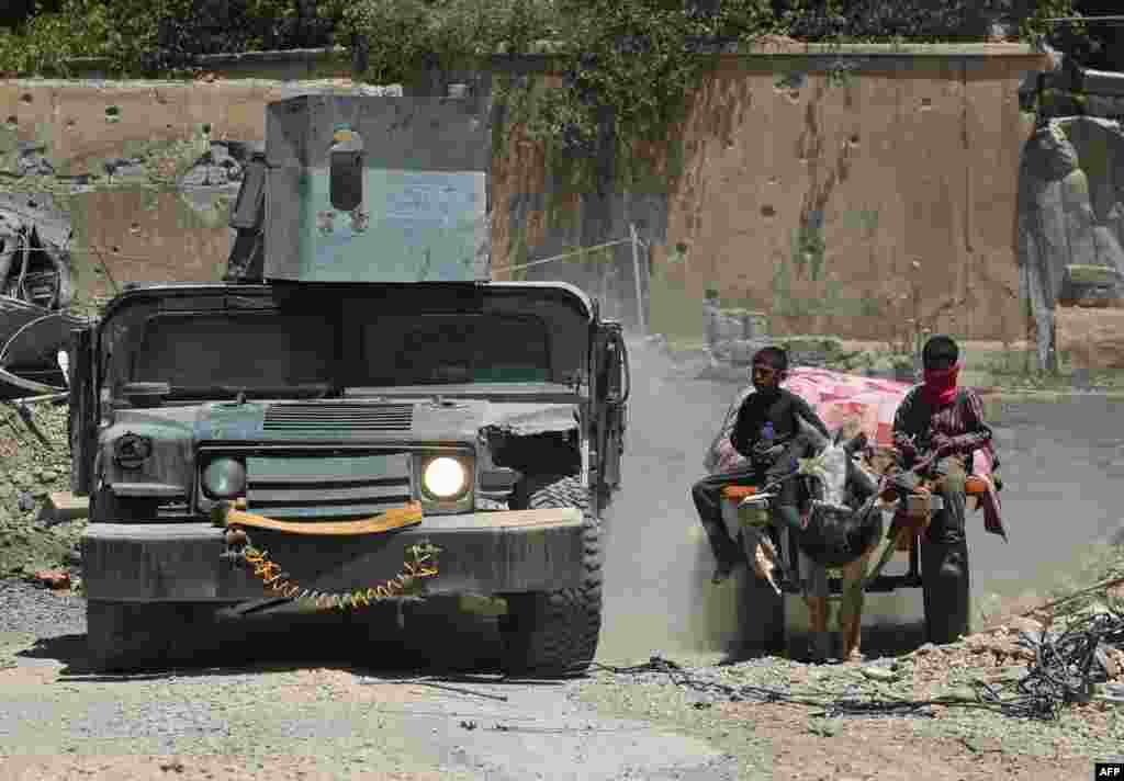 An Iraqi military vehicle passes displaced Iraqi boys returning to their homes in West Mosul's Oreibi neighborhood after government forces retook control of the area from the Islamic State (IS) group.