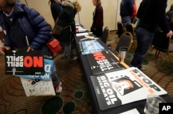 Signs opposing offshore oil drilling are distributed, March 5, 2018, at a hearing in Olympia, Wash., organized by a coalition of environmental groups opposed to the Trump administration's proposal to expand offshore oil drilling off the Pacific Northwest
