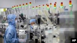 資料照片:2020年5月14日,佩戴保護設備的員工在北京記者的政府組織遊覽期間在瑞薩電子的半導體生產設施中工作。
