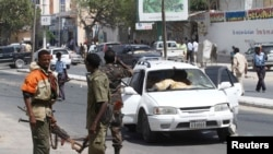 Somali government soldiers secure the scene of a car bomb attack in the capital Mogadishu, Feb. 10, 2014.