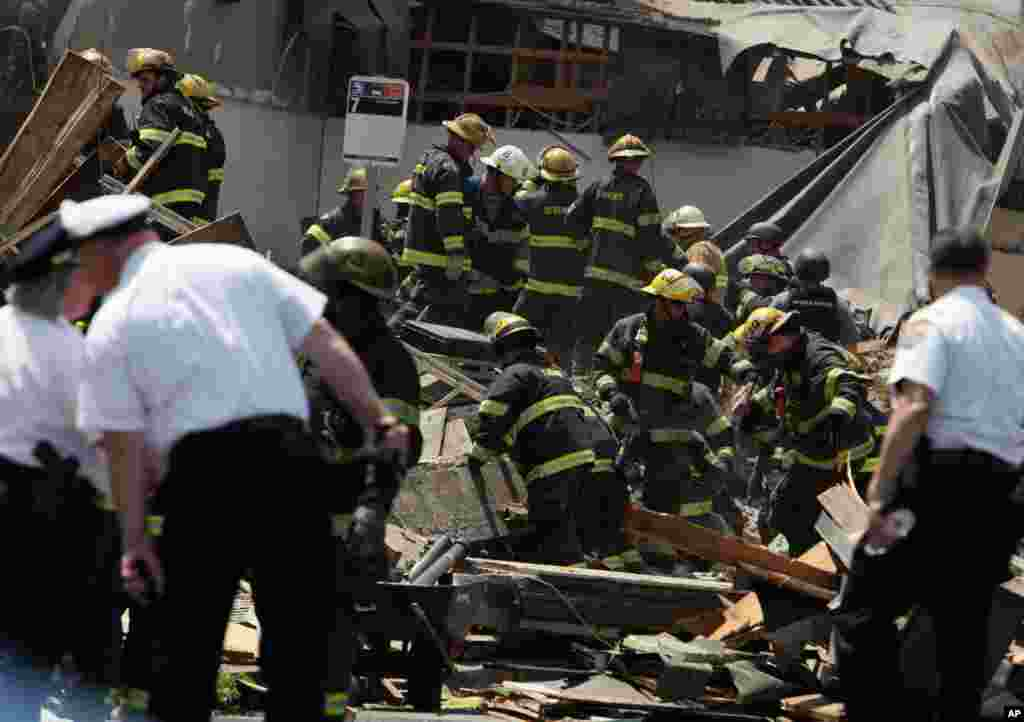 Rescue personnel search the scene of a building collapse in Philadelphia, Pennsylvania, June 5, 2013.
