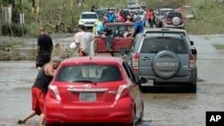 Residentes se mueven por una carretera inundada en Toa Baja, Puerto Rico.