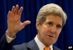 FILE - U.S. Secretary of State John Kerry applauds new Iraqi government.
