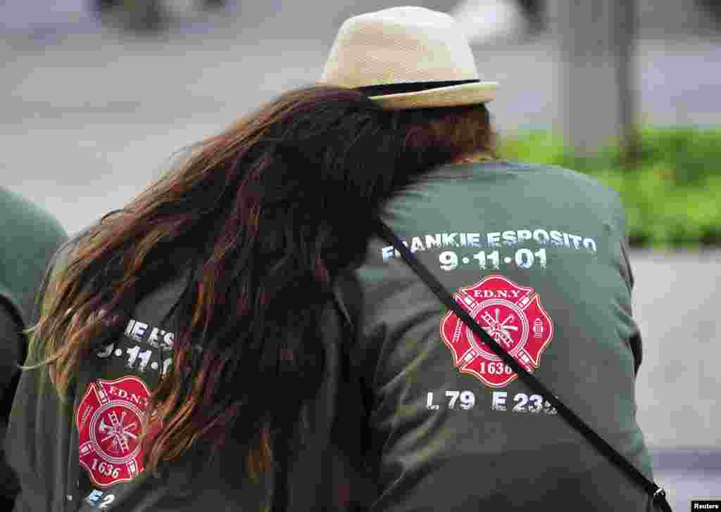 Two people with shirts commemorating New York City Fire Department firefighter Frankie Esposito sit at the South reflecting pool at the 9/11 Memorial during ceremonies marking the 12th anniversary of the 9/11 attacks on the World Trade Center in New York.