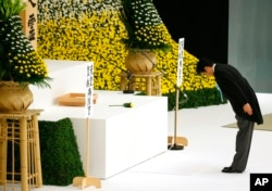 FILE - Japanese Prime Minister Shinzo Abe bows before the main altar decorated with huge bank of chrysanthemums as he offers prayers for the war dead during a memorial service at Nippon Budokan martial arts hall in Tokyo, Aug. 15, 2015.