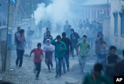 Police use teargas smoke to disperse protesters as Kashmiri Muslim villagers gather near the house of Zahid Ahmed before his body arrived at Batango village, south of Srinagar, Indian-controlled Kashmir, Oct. 18, 2015.
