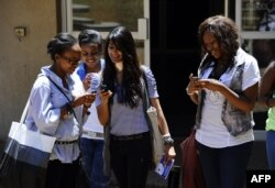 FILE - Students look at a new app on their mobile device, where they can receive and share information in real-time in the event of a health crisis, epidemic(s), and natural disasters.