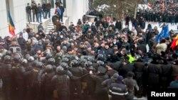 Para pengunjuk rasa berusaha menyerbu parlemen Moldova yang dijaga pasukan keamanan di Chisinau hari Rabu (20/1).