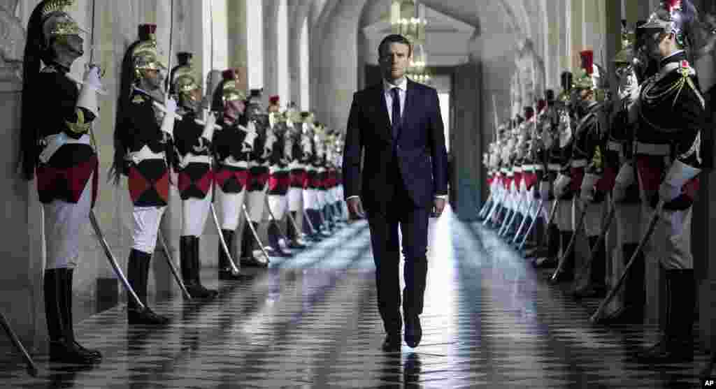 French President Emmanuel Macron walks through the Galerie des Bustes (Busts Gallery) to access the Versailles Palace's hemicycle where both houses of parliament (National Assembly and Senate) are gathered in the palace of Versailles, outside Paris. Macron laid out his political, security and diplomatic priorities at an extraordinary joint session of parliament at the chateau of Versailles.