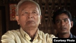 "Nuon Chea (left), ""Brother Number Two"" of the Khmer Rouge regime, sits with documentary filmmaker Thet Sambath during an interview."