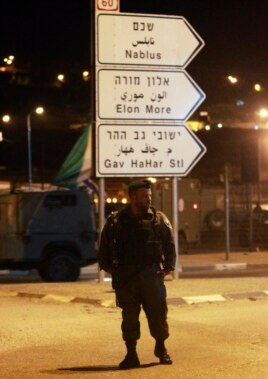 An Israeli soldier stands guard at the Zatra checkpoint near the West Bank city of Nablus, June 3, 2014.