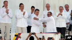Colombia's President Juan Manuel Santos, front left, and the top commander of the Revolutionary Armed Forces of Colombia (FARC) Rodrigo Londono, known by the alias Timochenko, shake hands after signing the peace agreement between Colombia's government and