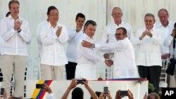 ປະທານາທິບໍດີ ໂຄລົມເບຍ ທ່ານ Juan Manuel Santos, ໜ້າຊ້າຍ, ແລະ ຜູ້ບັນຊາການຂັ້ນສູງຂອງກອງກຳລັງປະຕິວັດ ປະກອບອາວຸດແຫ່ງ ໂຄລົມເບຍ ທ່ານ Rodrigo Londono, ຈັບມືກັນຫຼັງຈາກເຊັນຂໍ້ຕົກລົງສັນຕິພາບ.
