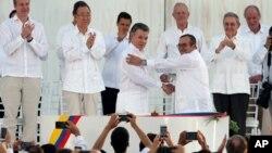 Presiden Kolombia Juan Manuel Santos (tengah kiri) berjabat tangan dengan komandan tertinggi pemberontak FARC, Rodrigo Londono usai penandatanganan perjanjian damai di Cartagena, Senin (26/9).