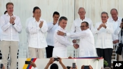 Colombia's President Juan Manuel Santos, front left, and the top commander of the Revolutionary Armed Forces of Colombia (FARC) Rodrigo Londono, shake hands after signing the peace agreement between Colombia's government and the FARC to end over 50 years of conflict in Cartagena, Colombia, Sept. 26, 2016.