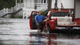 A Mississippi man lifts his left leg to remove water from his boot after wading through Isaac's flood waters