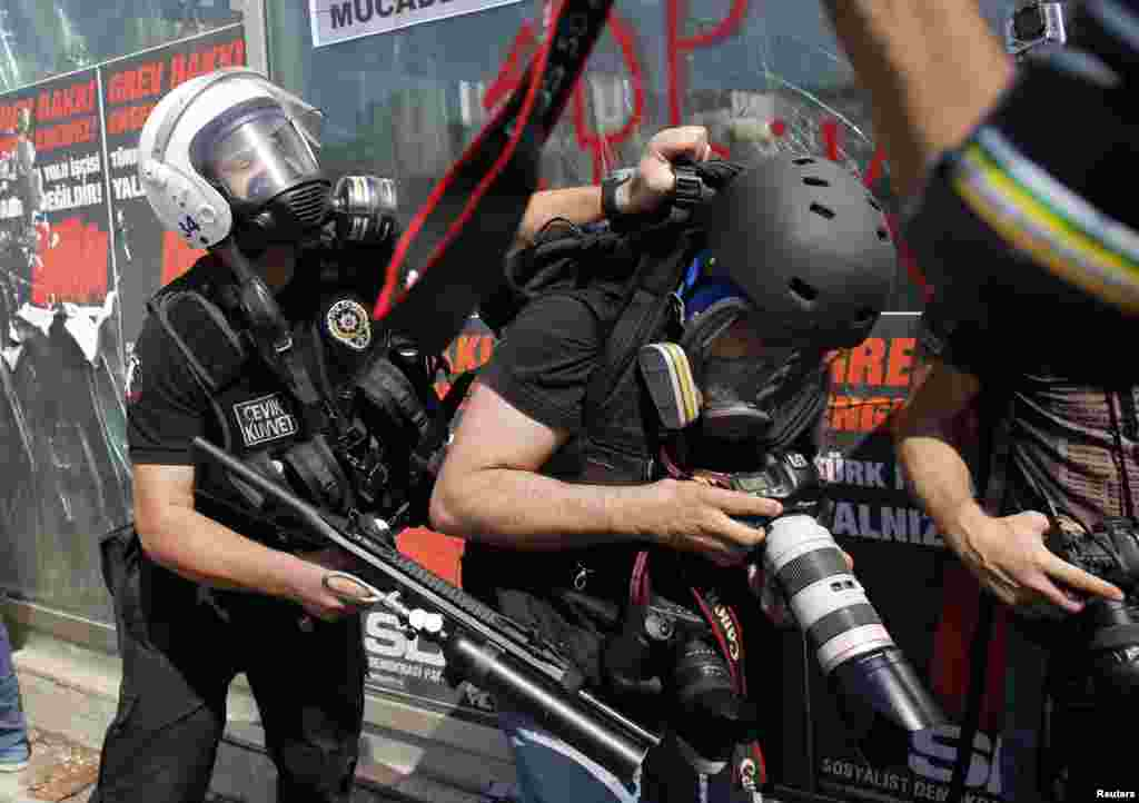 A Turkish riot police officer pushes a photographer during a protest in Taksim Square in Istanbul, June 11, 2013.