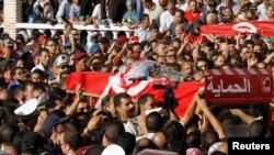 2013年10月24日突尼斯一名遇害警察的一些亲友和同事为他抬举棺木到坟场埋葬。