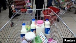 FILE - Food items are placed in trolleys as customers stand in line to pay for their goods at a shopping mall in northwestern Tehran, Iran.