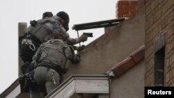 Les forces spéciales de la police belge sont sur le toit d'un immeuble au cours d'un raid, à la recherche de fondamentalistes musulmans présumés liés aux attentats meurtriers à Paris, à Molenbeek, dans la banlieue de Bruxelles, à Molenbeek, 16 novembre 2015.