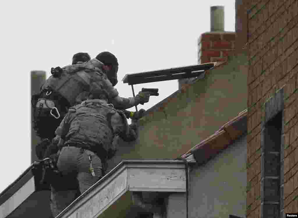 Belgian special forces police climb on an apartment block during a raid, in search of suspected Muslim fundamentalists linked to the deadly attacks in Paris, in the Brussels suburb of Molenbeek.